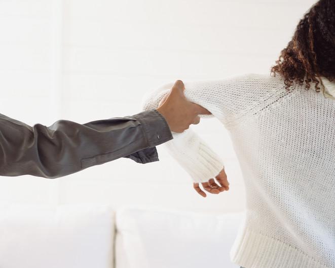 man grabbing womans arm