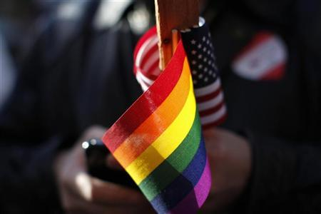 Marriage equality supporter Gus Thompson holds gay pride and American flags at a demonstration t the 9th District Court of Appeals in San Francisco